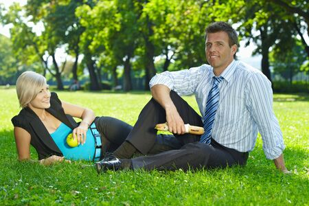 Young businesspeople sitting on grass and having lunch outdoor in city park summertime. Stock Photo - 6308435