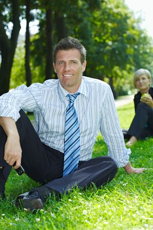 Businessman sitting in grass in park holding mobile. Busineswoman eating apple in background. photo