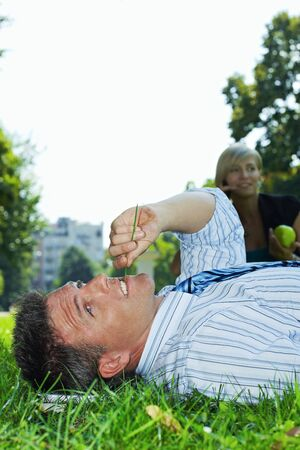 Businessman resting in grass in park, busineswoman talking on mobile in the background. Stock Photo - 6308388