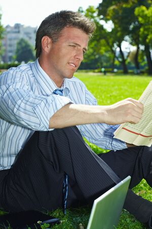 Relaxed businessman sitting in grass beside laptop computer, reading newspaper. Stock Photo - 6308430
