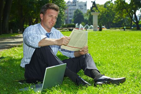 Relaxed businessman sitting in grass beside laptop computer, reading newspaper. Stock Photo - 6308431
