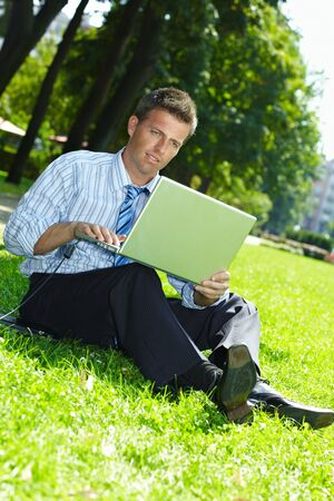 Relaxed businessman sitting in grass beside laptop computer, reading newspaper. Stock Photo - 6308439