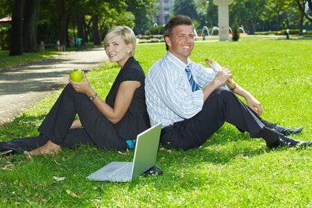 pausa: Empresarios j�venes sentados en el c�sped y almorzar en un parque de verano. Foto de archivo