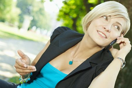 Young businesswoman talking on mobile phone in park, smiling. Stock Photo - 6308422