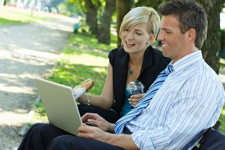 sandwitch: Young businesspeople sitting on bench in park having luch and looking at laptop computer. Stock Photo