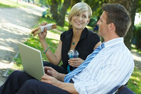 Young businesspeople sitting on bench in park having luch and looking at laptop computer. Stock Photo - 6308432