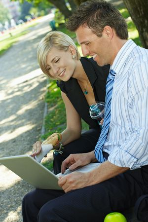 Young businesspeople sitting on bench in park having luch and looking at laptop computer. photo