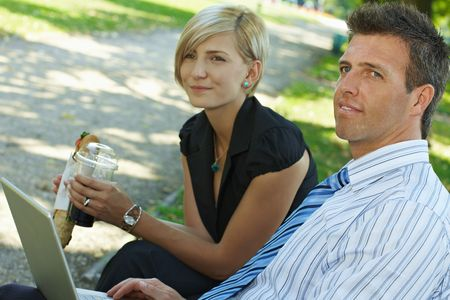 Young businesspeople sitting on bench in park having luch and looking at laptop computer. Stock Photo - 6308421