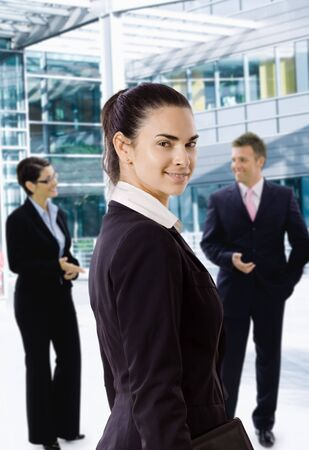 officetower: Young businesswoman standing in front of office building, looking back, smiling.