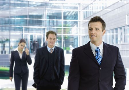 officetower: Young businessman leaving office building aong other businesspeople in the background. Stock Photo