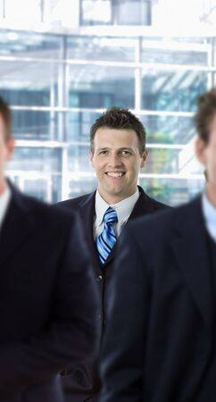 Happy businessman standing behind other businesspeople, in front of office building. photo