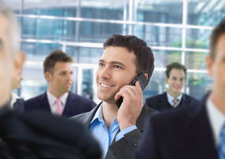 Happy businessman talking on mobile standing in crowd in office lobby. Stock Photo - 6338338