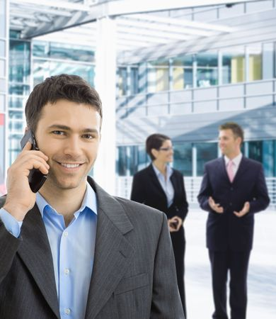 Portrait of happy businessman talking on mobile in office lobby. photo