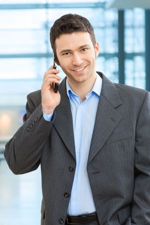 Portrait of happy businessman talking on mobile in office lobby. Stock Photo - 6338359