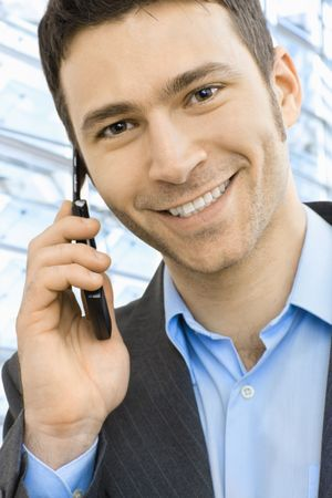 Closeup portrait of happy businessman talking on mobile in front of office building windows. Stock Photo - 6338363