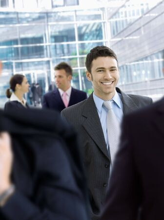 Young businessman walking in crowd in office lobby, smiling. photo