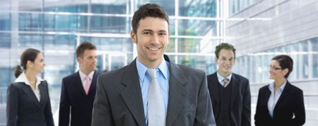 Portrait of happy businessman standing in office lounge, in front of business team, smiling. photo