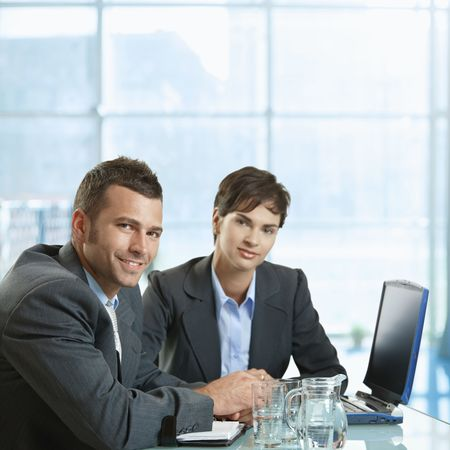 interacting: Businessman and businesswoman sitting at desk in office, using laptop computer, smiling. Stock Photo
