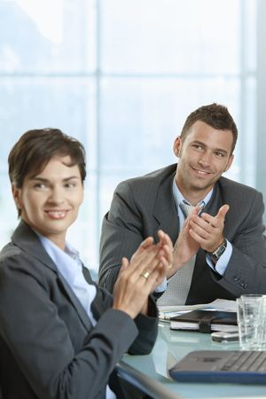 Businessman and businesswoman sitting at desk in meeting room, clapping hands. photo