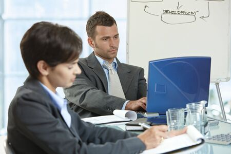 Businessman and businesswoman sitting at desk in office, using laptop computer and writing notes. photo