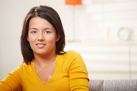 Casual teen girl sitting on sofa at home, looking at camera, smiling. Stock Photo - 6338354