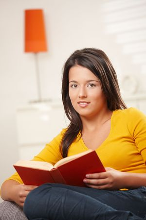 Casual teen girl sitting on sofa at home, reading book, looking at camera, smiling. Stock Photo - 6338348