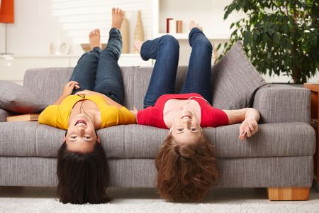 Teenage girls lying on couch upside down, looking at camera, smiling. Stock Photo - 6338364