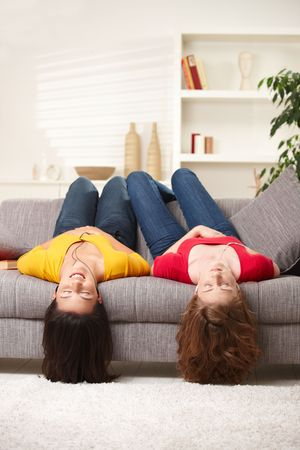 Teen girls lying on couch upside down, listening to music in earbuds, eyes closed. photo
