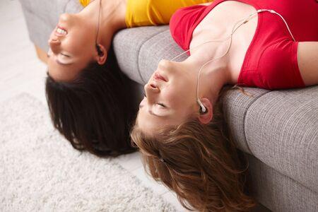 ojos cerrados: Las ni�as adolescentes acostado boca abajo de sof�, escuchar m�sica, ojos cerrados.