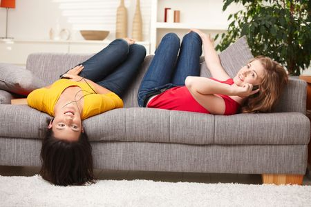 lay down: Happy teenage girls lying on sofa, listening to music and having fun at home.
