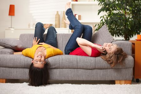 listening back: Happy teen girls resting on sofa at home, smiling.
