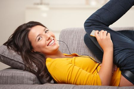 Happy teen girl lying on sofa at home listening music on earphones, smiling. photo