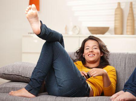 Happy teen girl lying on sofa at home listening music on earphones, smiling. Reklamní fotografie - 6338356