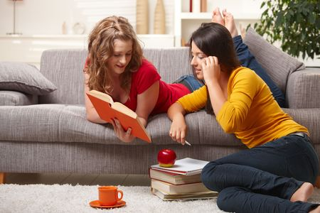 sitting room: Happy highscool students learning at home, smiling.