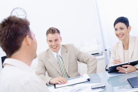 Happy businesspeople conducting job interview in brightly lit office, smiling. photo