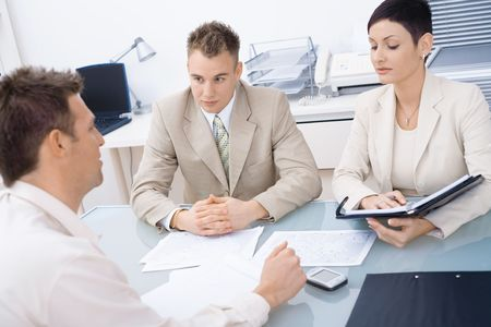 mediation: Businesspeople conducting job interview in brightly lit office.