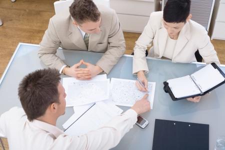 ハイアングルビュー: 3 机、ハイアングルの周りに座って、一緒に働いて良心的。 写真素材