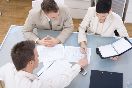 revisando documentos: Businessteam de tres trabajando juntos, sentados alrededor de una mesa, vista de �ngulo alto.