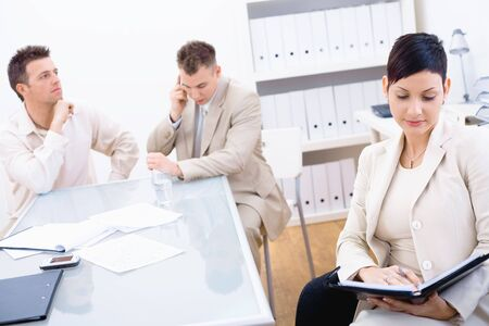 Young businesspeople sitting at office desk. Businesswoman looking at personal organizer, businessman talking on mobile. photo