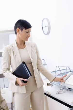 Young businesswoman wearing beige suit taking up landline phone in office. photo