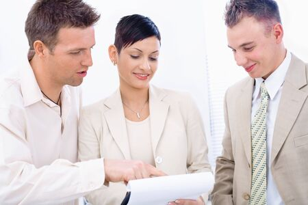 Three young businesspeople having business meeting, looking at document and smiling. photo