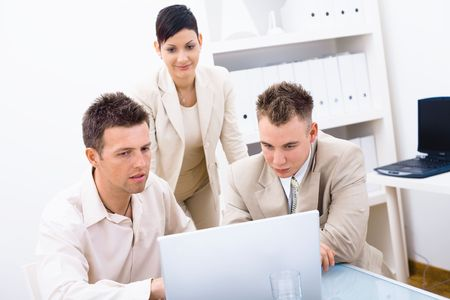 Group of young businesspeople working together in office, using laptop computer. Stock Photo - 6338434