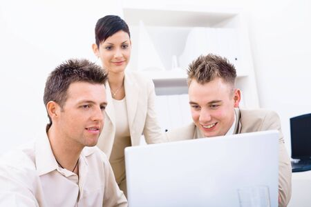 Group of young businesspeople working together in office, using laptop computer. photo