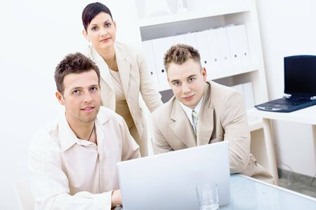 Three businesspeople working together in office, using laptop computer, looking at camera, smiling. photo