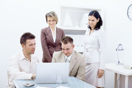 Business team working together in office, looking at laptop computer screen, smiling. photo