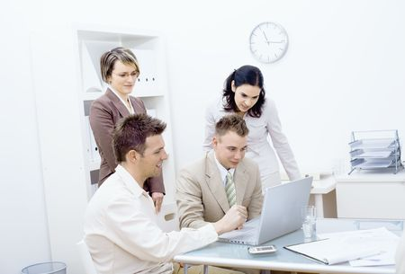 Business team working together in office, looking at laptop computer screen, smiling. Stock Photo - 6338407