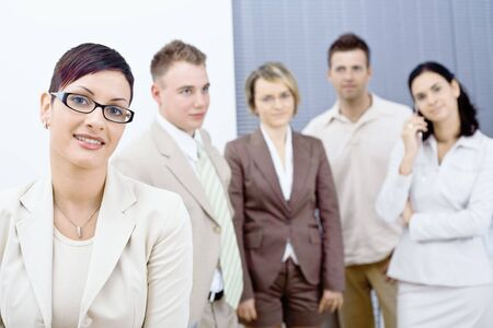 Young businesswoman wearing glasses posing in front, looking at camera, smiling. Four businesspersons standing in the background. photo