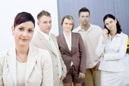 open collar: Young businesswoman wearing glasses posing in front, looking at camera, smiling. Four businesspersons standing in the background. Stock Photo