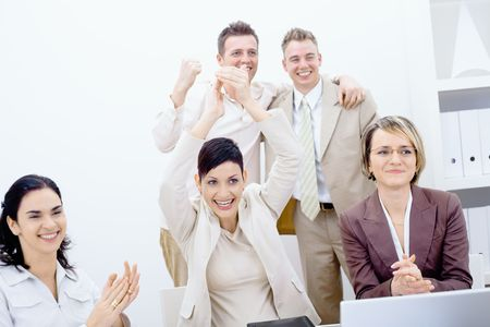 Group of five happy business people smiling and clapping, celebrating business success. photo