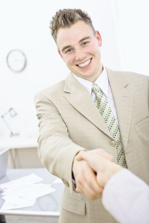 Happy businessmen shaking hands with somebody in office, smiling. photo